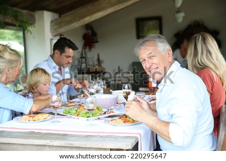 Family having summmer lunch in country house - stock photo