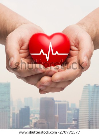 family health, charity and medicine concept - close up of hands holding red heart with cardiogram over city skyscrapers background - stock photo