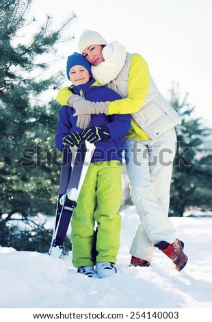 Family healthy lifestyle! Mother and son skiing in the forest, sunny winter day - stock photo