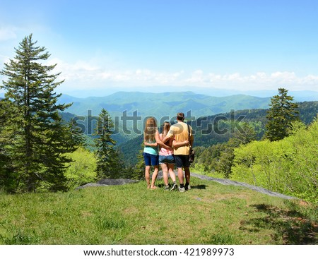 Family hiking in the mountains, father with arms around his daughter and wife looking at beautiful summer mountains landscape. Blue sky in the background. North Carolina, USA. - stock photo