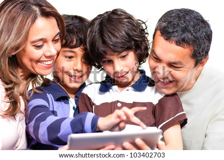 Family holding a tablet computer and looking at it - stock photo