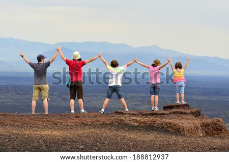 Family holding hands and arms up enjoying view of landscape on vacation - stock photo