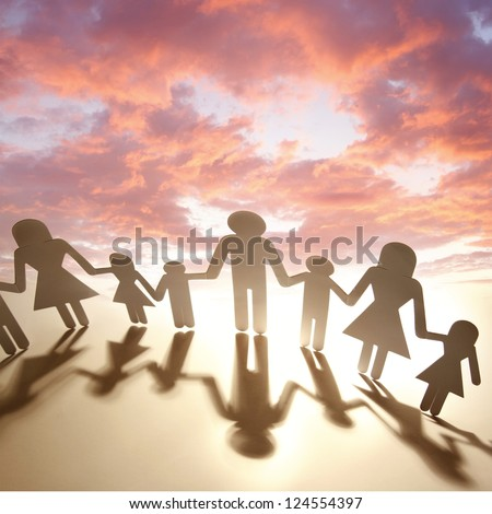 Family holding hands in front of sunset - stock photo