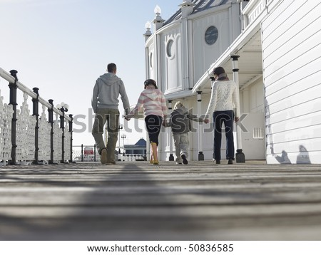Family holding hands, walking along pier, back view, low angle view - stock photo