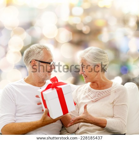 family, holidays, christmas, age and people concept - happy senior couple with gift box over lights background - stock photo