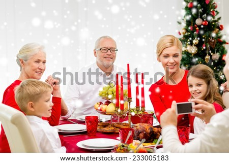 family, holidays, generation, christmas and people concept - smiling family having dinner and making photo with camera at home - stock photo