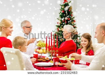 family, holidays, generation, christmas and people concept - smiling family having dinner at home - stock photo