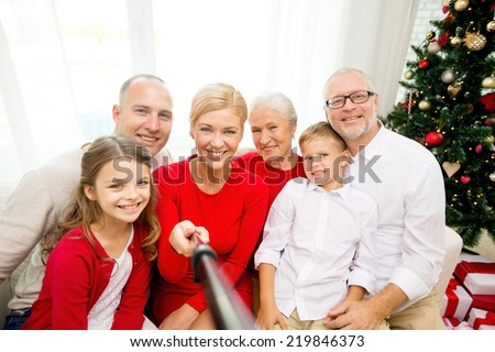 family, holidays, generation, christmas and people concept - smiling family with camera and selfie stick making picture at home - stock photo