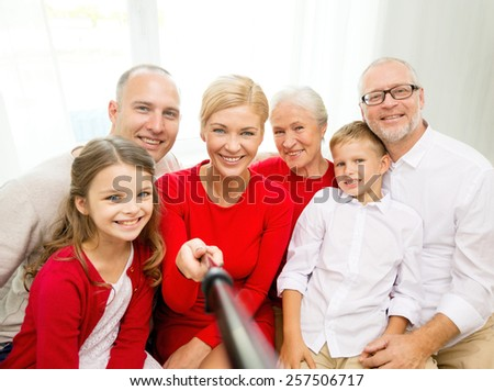 family, holidays, generation, christmas and people concept - smiling family with camera and stick making picture at home - stock photo