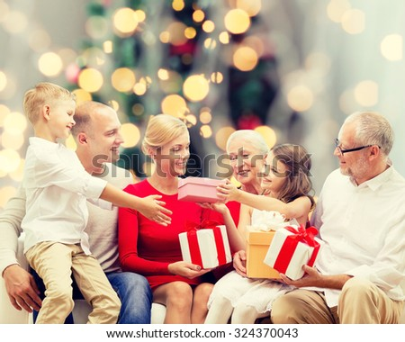 family, holidays, generation, christmas and people concept - smiling family with gift boxes sitting on couch over tree lights background - stock photo