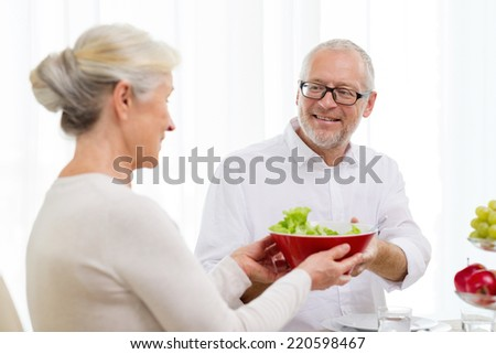 family, holidays, thanksgiving, christmas and people concept - smiling senior couple having dinner at home - stock photo