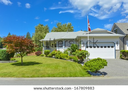 Family house on a sunny day with Canadian flag on the front yard and blue sky background. British Columbia, Canada. - stock photo