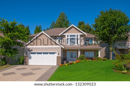 Family house with landscaping on the front and blue sky on background - stock photo