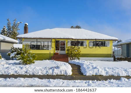 Family houses at winter season. Residential house in snow on a sunny day. Yellow house in snow on blue sky background. - stock photo