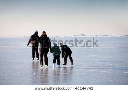 Family ice skating in natural rink frozen sea - stock photo