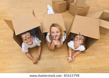 Family in a new home with cardboard boxes - having fun on the floor - stock photo
