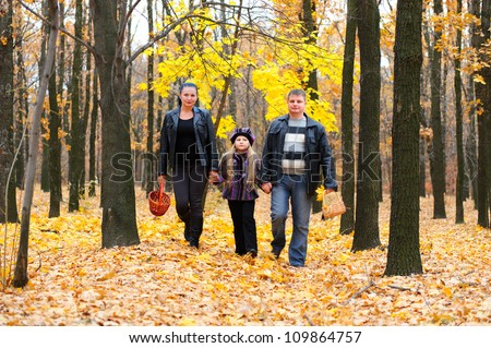Family in autumn forest. Walk for hands of a happy family from three persons - stock photo