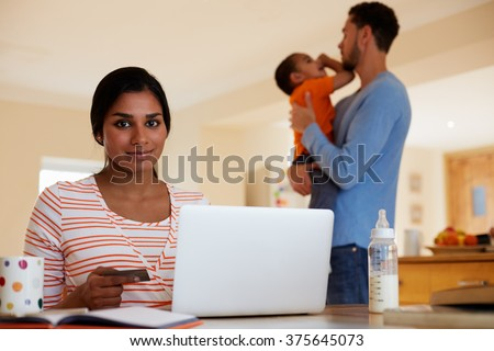 Family In Kitchen With Mother Making On Line Purchase - stock photo