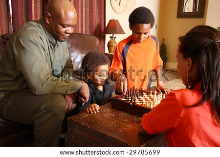 Family in living room playing chess together - stock photo