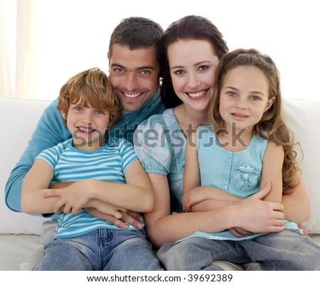 Family in living-room sitting on sofa together - stock photo