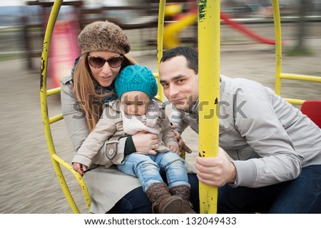 Family  in motion blur on a rotating swing with their daughter. - stock photo