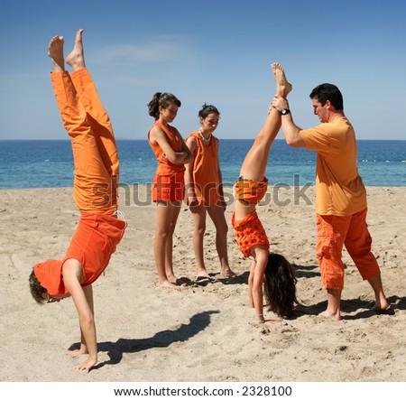 Family in orange clothes having fun on the beach - stock photo