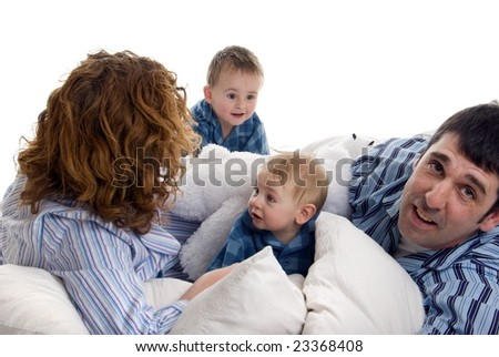Family in pajamas on bed - stock photo