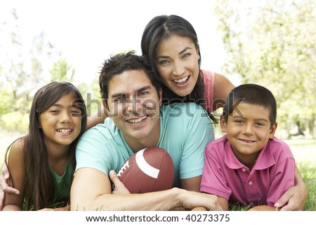 Family In Park With American Football - stock photo