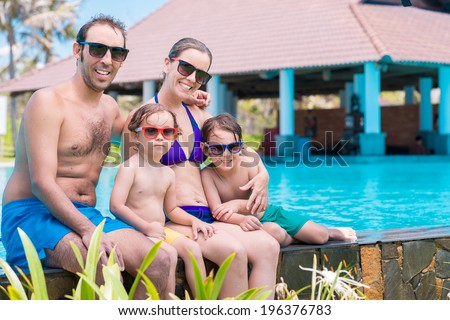 Family in sunglasses and bathing suits bonding together - stock photo