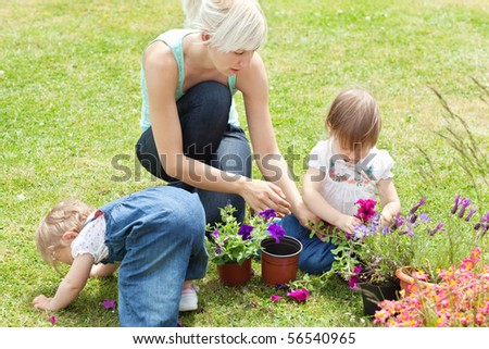 Family in the garden with flowers in the sunshine - stock photo