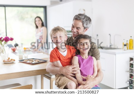 family in the kitchen at breakfast children on their father's lap - stock photo