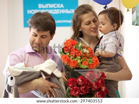 Family in the maternity hospital, father holds infant, mother with flowers holds elder son - stock photo