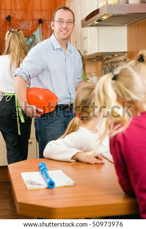 Family in the morning gathering in the kitchen, dad is ready to go to his work as a construction worker - stock photo