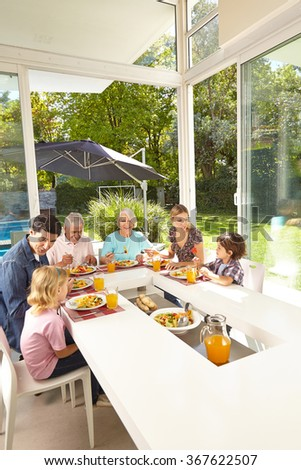 Family in three generations eating together at lunch table in summer - stock photo