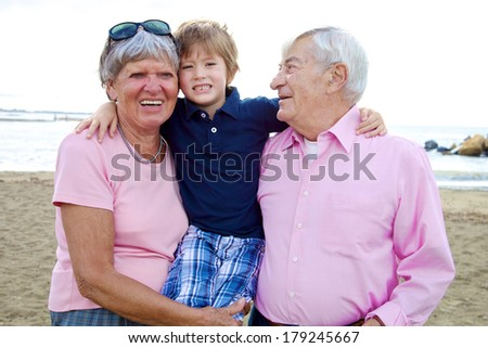 Family in vacation hugging child with grandma and grandpa - stock photo