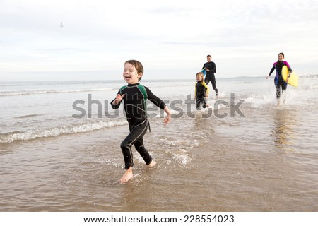 Family in Wetsuits on the Beach Playing in the Sea - stock photo