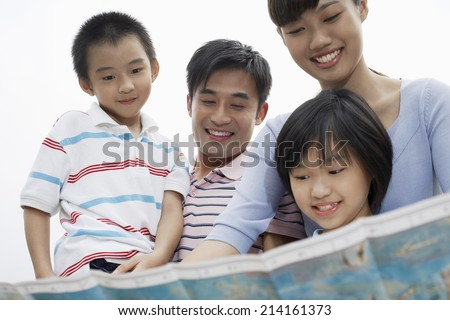 Family including boy and girl (7-9) reading map outdoors - stock photo