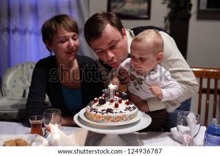 Family is blowing out candle on a birthday cake - stock photo