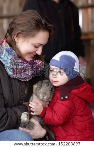 Family is holding rabbit on a farm - stock photo