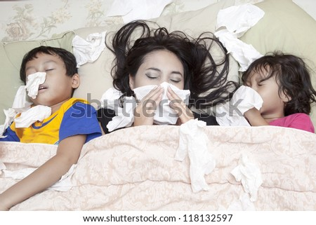 Family is lying on a bed due to flu in winter - stock photo