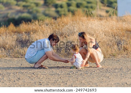 family is playing with child on road - stock photo