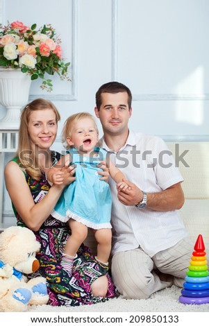 Family is sitting in living room smiling - stock photo
