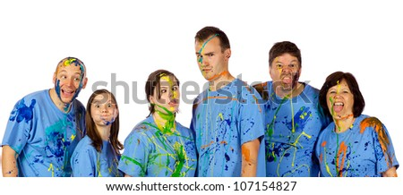 Family just got done having a paint fight and are making faces at the camera - stock photo