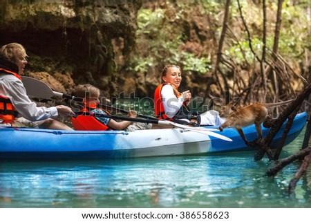 family kayaking on the mangroves and feeding monkeys - stock photo