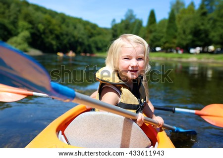 Family kayaking on the river on sunny summer day. Happy little child having fun enjoying adventurous experience. Water sport activities day during summer vacation. - stock photo