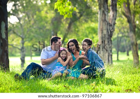 Family laughing during picnic in the park - stock photo
