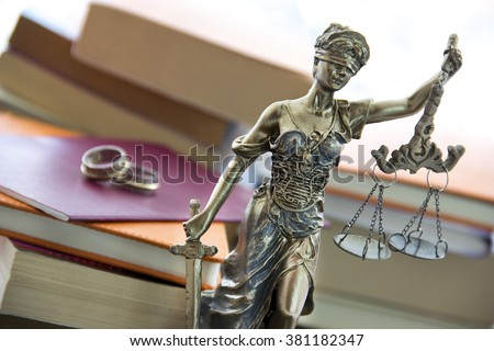 Family law. Justice statue with sword and scale and marriage certificate - stock photo