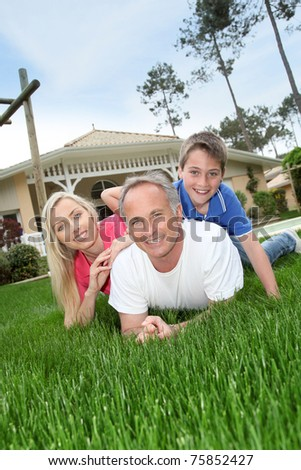 Family laying down in house garden - stock photo
