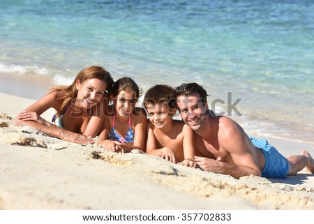 Family laying on a sandy beach - stock photo