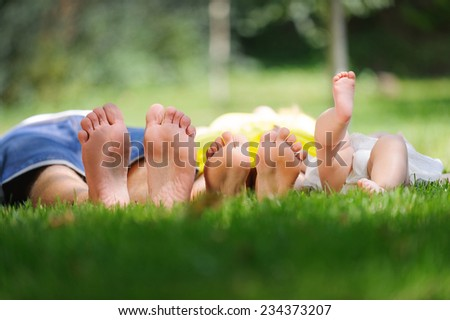 family laying on grass in park - stock photo